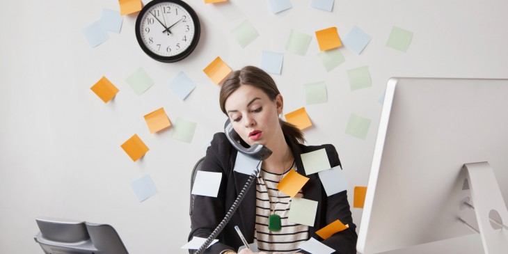 Studio shot of young woman working in office covered with adhesive notes